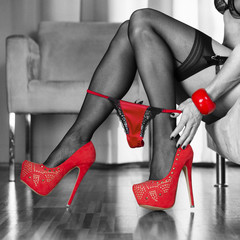 woman in red high heels shoes is pulling panties down