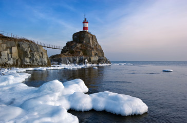 Winter picture lighthouse on a lonely rock.