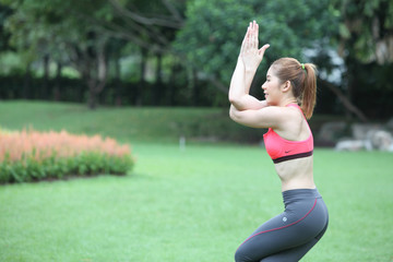 Half portrait Young Woman in engle arms Yoga Pose on lawn