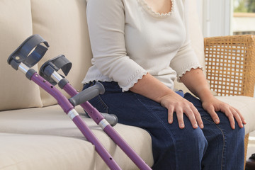 Woman with Cerebral Palsy sitting on couch with her crutches