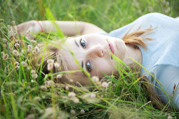 Beautiful young girl with freckles is lying on the grass