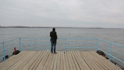 Sad pensive man standing on the pier and looking at the river