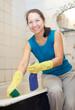 woman cleans bathroom