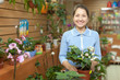 Happy mature woman at flower store