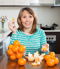 Smiling woman eating mandarins