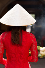 Woman in ao dai dress and conical hat