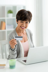 Mature woman with laptop and credit cart