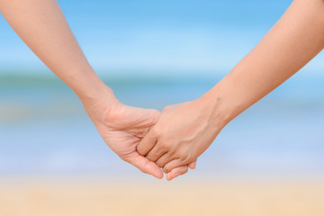 friend holding hand together and the sea background