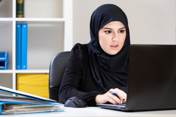 Muslim woman working on laptop