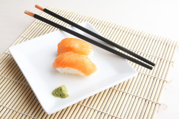 Plate of salmon sushi on bamboo mat