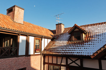 Tiled roof of a house with chimney, antenna and snow