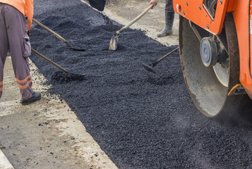 Workers patching asphalt