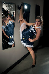 Young beautiful woman posing in sailor costume near the mirror