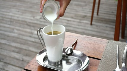 Pouring milk into the coffee cup