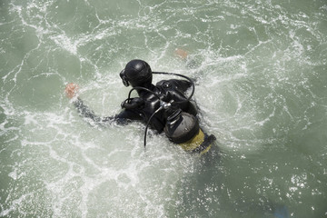 Commercial diver entering the water with a splash