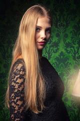 Sensual woman in black dress on green vintage interior