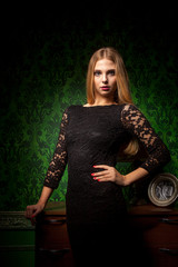 Gorgeous woman in green vintage room in black dress