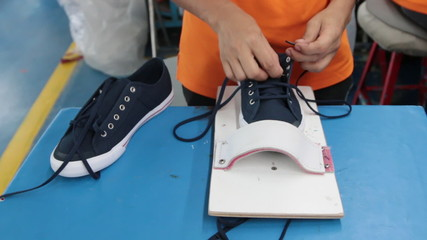 worker lacing the sneaker shoe with cotton lace