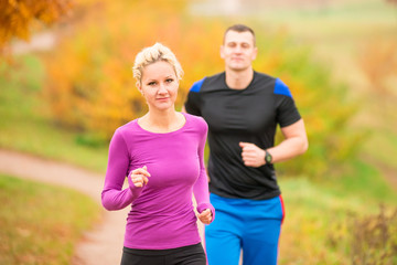 woman and man in autumn park on morning jog