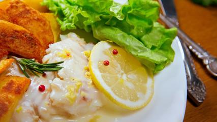 Lemon baked Haddock with fried Potatoes. Lemon sause,