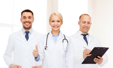 group of doctors showing thumbs up in clinic