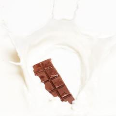 Dark chocolate splashed into fresh milk with white background.