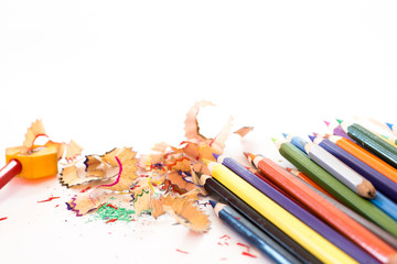 colorful pencils and pencils shaving on white background