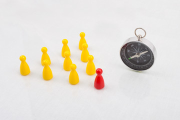 Leadership concept with pawns and compass