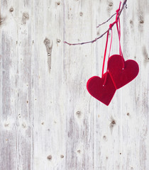 two red hearts, hanging on a branch over the  wooden background.