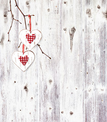 Two hearts, hanging on a branch over the old wooden background.