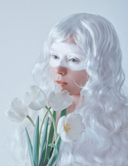 Spring fairy. Young woman in white wig with bouquet of tulips on