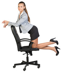 Businesswoman kneeling on office chair, looking at camera