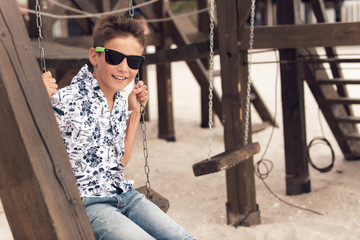 happy smiling adolescent boy in sunglasses  on a swing