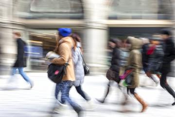 A shopper walking in front of shop window