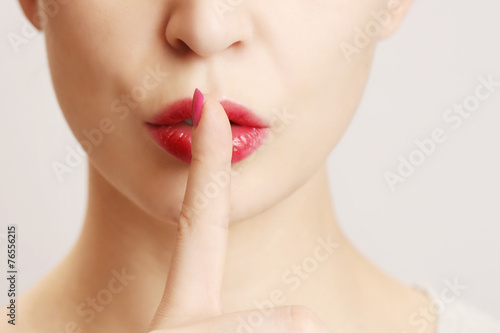 Finger on lips - silent gesture - 76556215