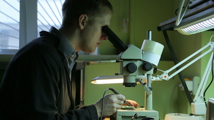 Scientist solder, looking through a microscope in the laboratory