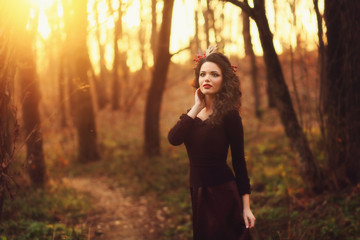 Portrait of a cute brunette mysterious at sunset in the forest