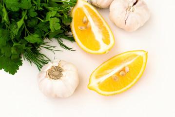 slices of lemon, garlic cloves and parsley on white background