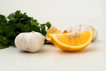 slices of lemon, garlic cloves and parsley on the white backgrou