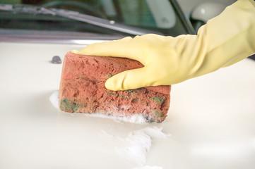 Male hand washing white car