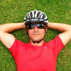 Ciclista tumbado sobre el césped