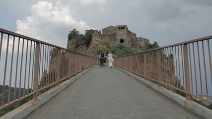 tourists walking on a uphill road  to reach a medieval village - steep - hill