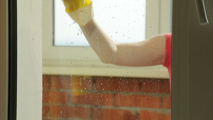 Girl washes the window in the kitchen at home, close-up