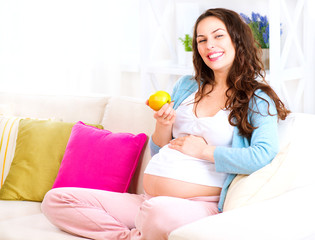 Pregnant Happy Woman sitting on a sofa and eating apple