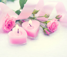 Valentine's Day. Pink heart shaped candles and rose flowers