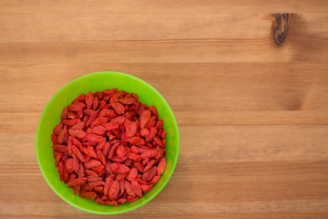 dried goji berries in green bowl on wooden table