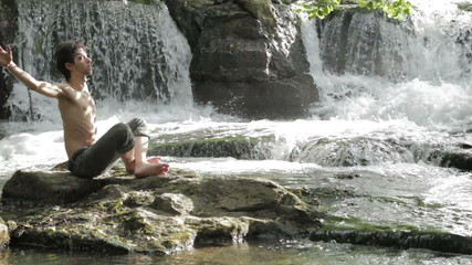 man makes physical exercises to keep fit , near wonderful waterfalls