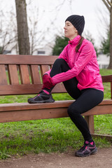 Sad young female athlete sitting on a bench