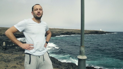 Handsome male jogger resting standing on rocks by sea