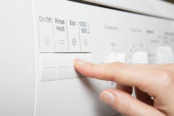 Woman Selecting Economy Program On Washing Machine To Save Energ